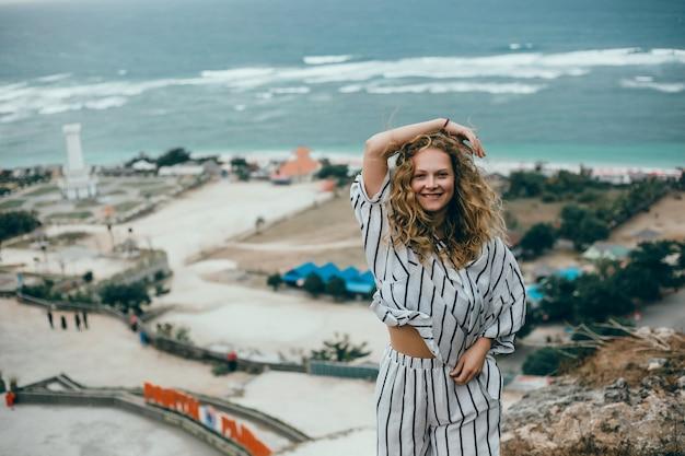 Młoda Piękna Dziewczyna Pozuje Na Plaży, Oceanu, Fale, Jasne Słońce I Opalona Skóra Darmowe Zdjęcia