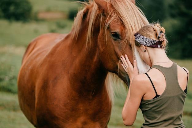Młoda Piękna Dziewczyna Przytulanie Konia W Przyrodzie Premium Zdjęcia