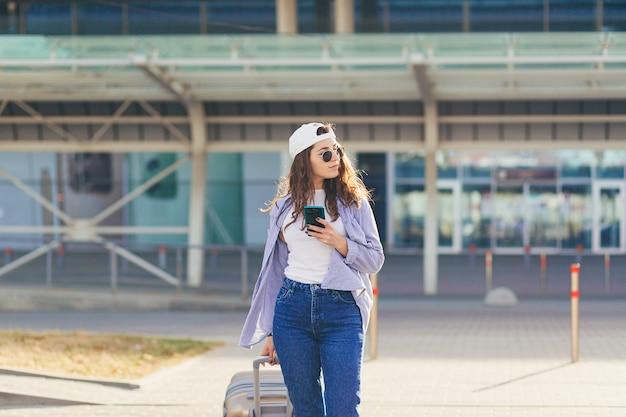 Młoda Piękna Dziewczyna Rozmawia Przez Telefon W Pobliżu Dużego Przystanku Autobusowego Z Walizką Premium Zdjęcia