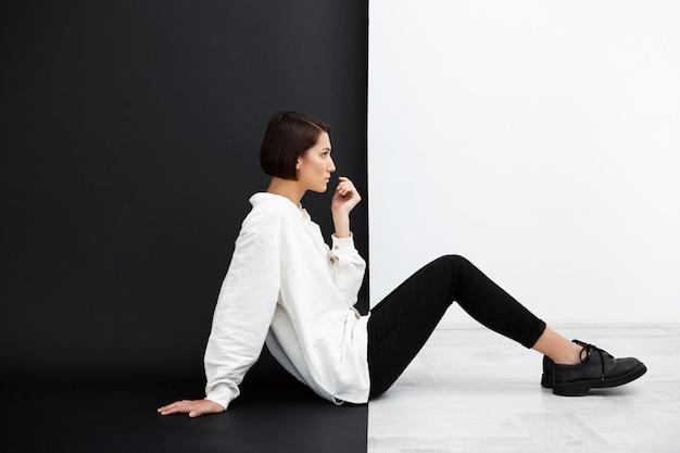 Młoda Piękna Dziewczyna Siedzi Na Podłodze Nad Czarno-białe ściany Darmowe Zdjęcia