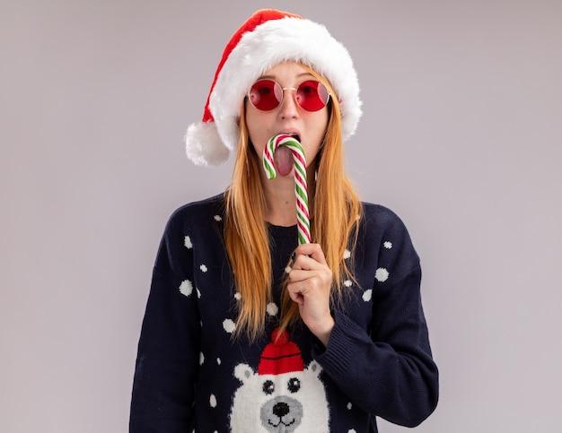 Młoda Piękna Dziewczyna Ubrana W świąteczny Kapelusz I Okulary, Trzymając I Lizanie świąteczne Cukierki Na Białym Tle Na Białej ścianie Darmowe Zdjęcia