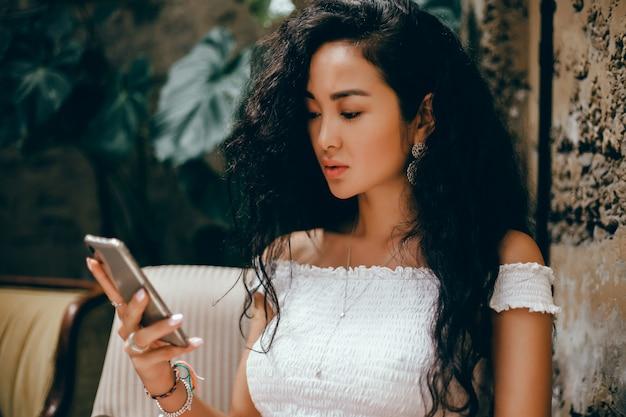 Młoda Piękna Dziewczyna Używa Smartfona Na Ulicy, Surfując W Internecie Darmowe Zdjęcia
