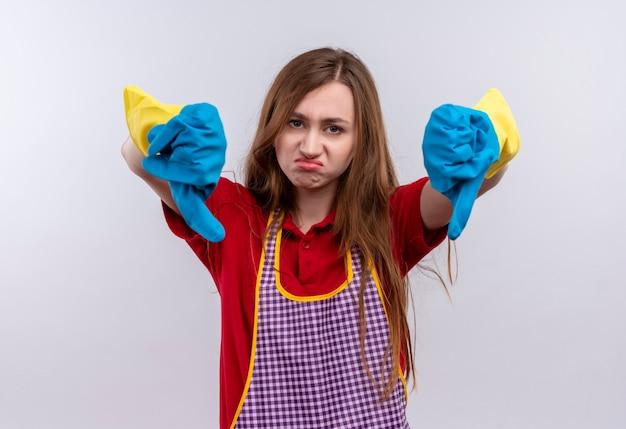 Młoda Piękna Dziewczyna W Fartuch I Gumowe Rękawiczki Patrząc Na Kamery Niezadowolona Pokazując Kciuki W Dół Obiema Rękami Darmowe Zdjęcia