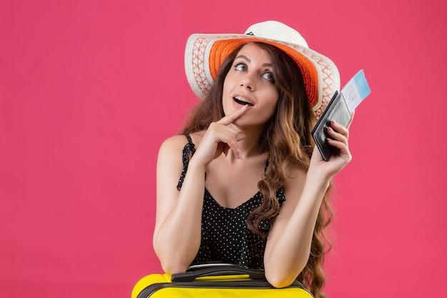 Młoda Piękna Dziewczyna W Sukience W Kropki W Letnim Kapeluszu Trzyma Bilety Lotnicze Patrząc Z Boku Z Zamyślonym Wyrazem Myśli Pozytywnej Pozycji Na Różowym Tle Darmowe Zdjęcia