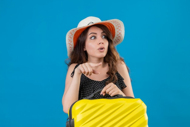 Młoda Piękna Dziewczyna W Sukience W Kropki W Letnim Kapeluszu Trzyma Walizkę Wskazując Palcem W Bok, Patrząc Zaskoczony Stojąc Na Niebieskim Tle Darmowe Zdjęcia