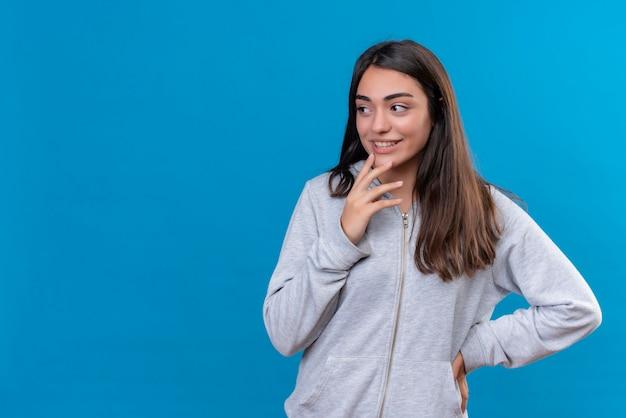 Młoda Piękna Dziewczyna W Szary Bluza Z Kapturem, Odwracając Wzrok Z Zamyślonym Wyrazem Twarzy Myślenia Stojącego Na Niebieskim Tle Darmowe Zdjęcia
