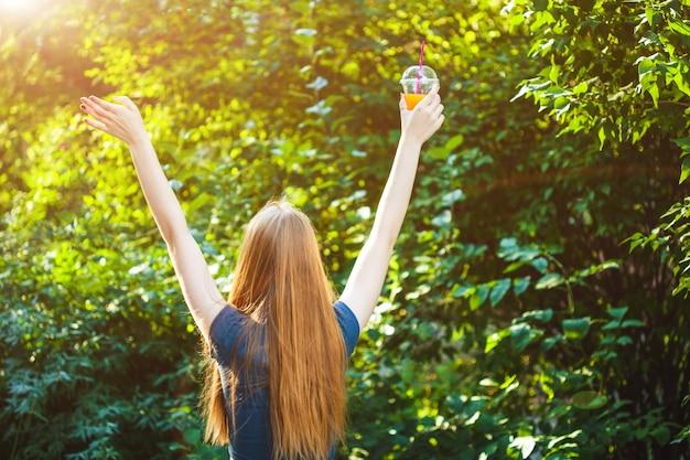 Młoda Piękna Dziewczyna Wyciąga Ręce Do Słońca, Trzymając W Ręku Sok. Premium Zdjęcia