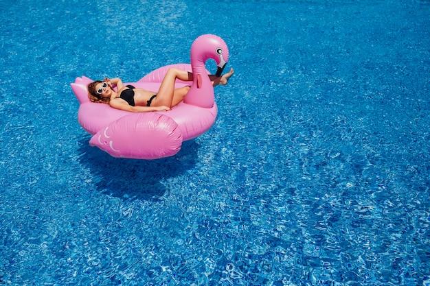 Młoda piękna dziewczyna z piękną postacią w czarnym kostiumu kąpielowym i okularach przeciwsłonecznych Premium Zdjęcia