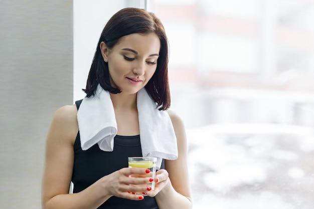 Młoda piękna fitness kobieta w odzieży sportowej z ręcznikiem Premium Zdjęcia