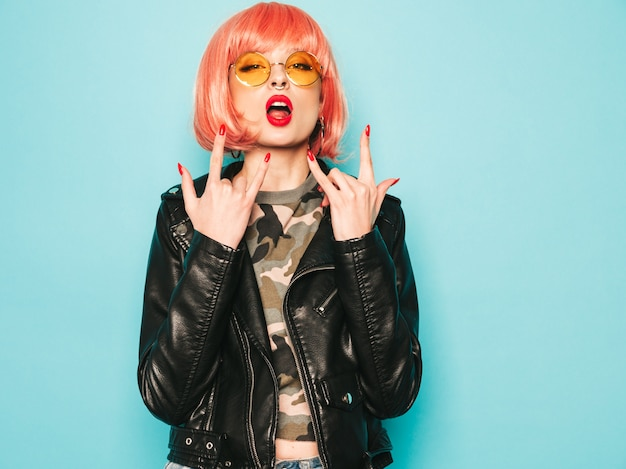 Młoda Piękna Hipster Zła Dziewczyna W Czarnej Skórzanej Kurtce I Kolczyk W Nosie. Seksowna Beztroska Kobieta Pozuje W Studiu W Różowej Peruce Blisko Błękitnej ściany. Pewny Siebie Model W Okularach Przeciwsłonecznych. Pokazuje Rock And Roll Znaka Darmowe Zdjęcia