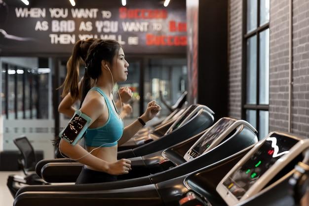 Młoda piękna kobieta azji działa na bieżni w siłowni. Premium Zdjęcia