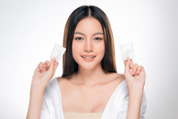 Młoda piękna kobieta czyści twarz bawełną Premium Zdjęcia