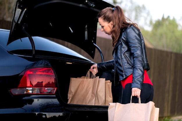 Młoda Piękna Kobieta Idzie Do Samochodu Z Zakupów W Supermarkecie Premium Zdjęcia