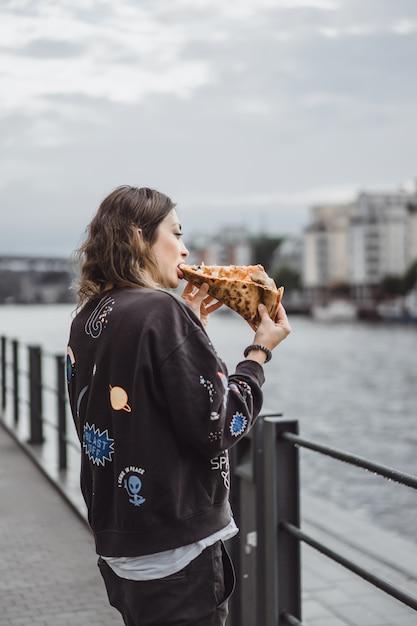 Młoda piękna kobieta je plasterek pizza na miasto ulicie Darmowe Zdjęcia