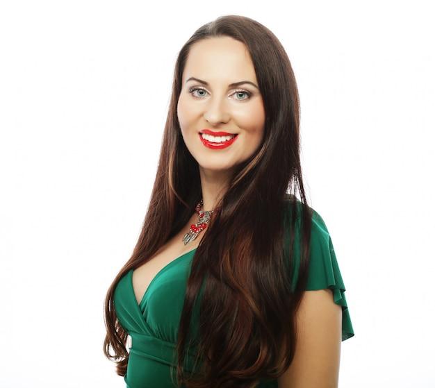 Młoda piękna kobieta jest ubranym zieleni suknię Premium Zdjęcia