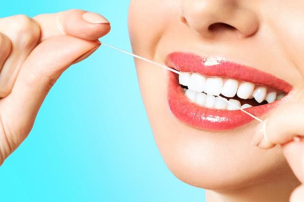 Młoda Piękna Kobieta Jest Zaangażowana W Czyszczenie Zębów. Piękny Uśmiech, Zdrowe, Białe Zęby. Dziewczyna Trzyma Nić Dentystyczną. Pojęcie Higieny Jamy Ustnej. Premium Zdjęcia