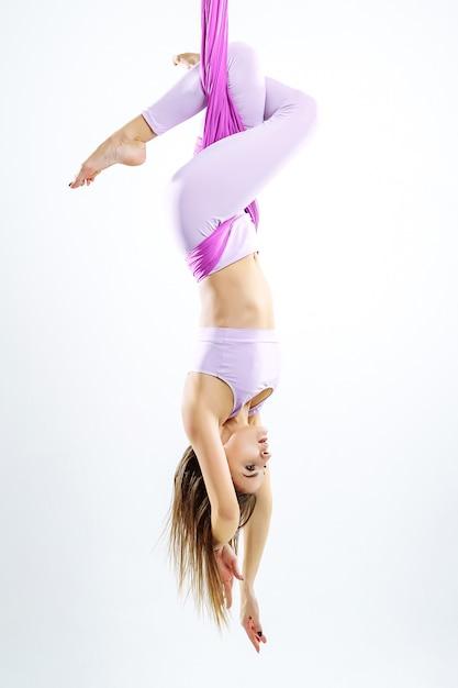Młoda piękna kobieta jogin robi aerial joga praktyka w fioletowy hamak. Premium Zdjęcia