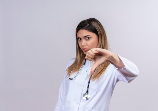 Młoda Piękna Kobieta Lekarz Ubrany W Biały Fartuch Ze Stetoskopem, Patrząc Z Marszczącą Brwią Twarz Pokazującą Niechęć Darmowe Zdjęcia