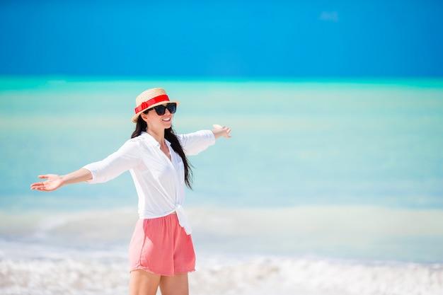 Młoda piękna kobieta na białego piaska tropikalnej plaży. kaukaska dziewczyna z kapeluszowym tłem morze Premium Zdjęcia