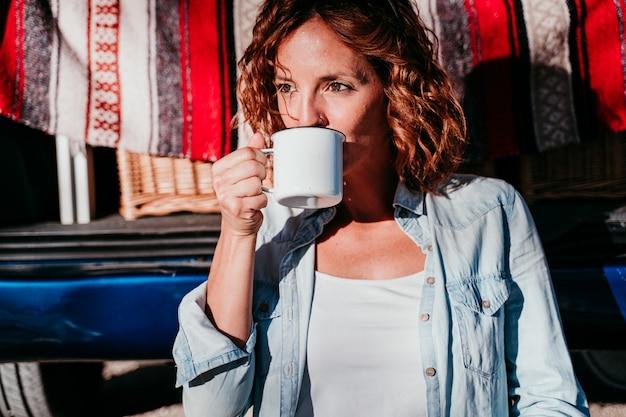 Młoda Piękna Kobieta Pije Kawę Lub Herbatę Obozuje Na Zewnątrz Z Vanem I Jej Dwoma Psami. Koncepcja Podróży Premium Zdjęcia