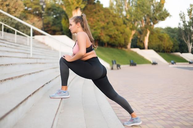 Młoda Piękna Kobieta Plus Size W Sportowej Bluzce I Legginsach Rozmarzonym Rozciąganiem Na Schodach W Parku Miejskim Na świeżym Powietrzu Premium Zdjęcia