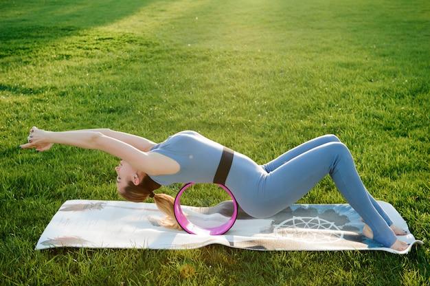 Młoda Piękna Kobieta Robi Joga ćwiczeniom W Parku Premium Zdjęcia