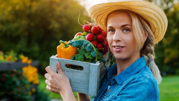 Młoda Piękna Kobieta Rolnik Kapelusz Z Pudełko świeżych Ekologicznych Warzyw Premium Zdjęcia