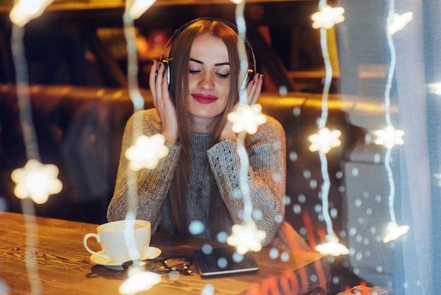 Młoda piękna kobieta siedzi w kawiarni, picia kawy. model słuchania muzyki. boże narodzenie, nowy rok, walentynki, ferie zimowe Premium Zdjęcia