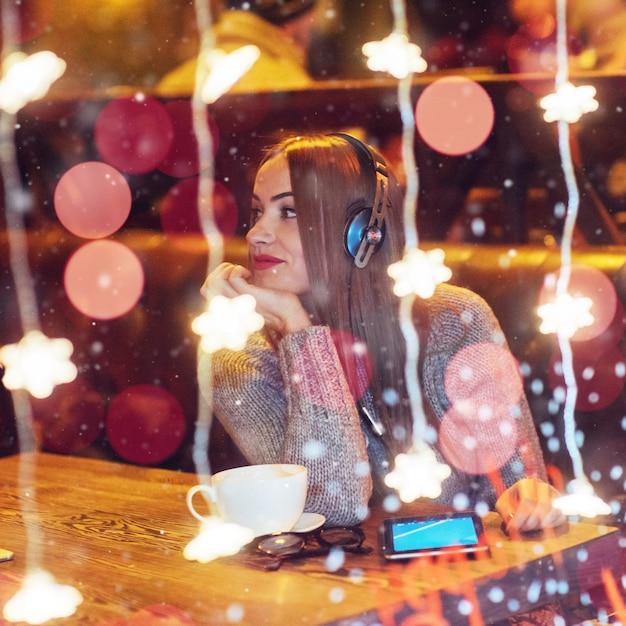 Młoda piękna kobieta siedzi w kawiarni, picia kawy. model słuchania muzyki. boże narodzenie, szczęśliwego nowego roku, walentynki, ferie zimowe Premium Zdjęcia