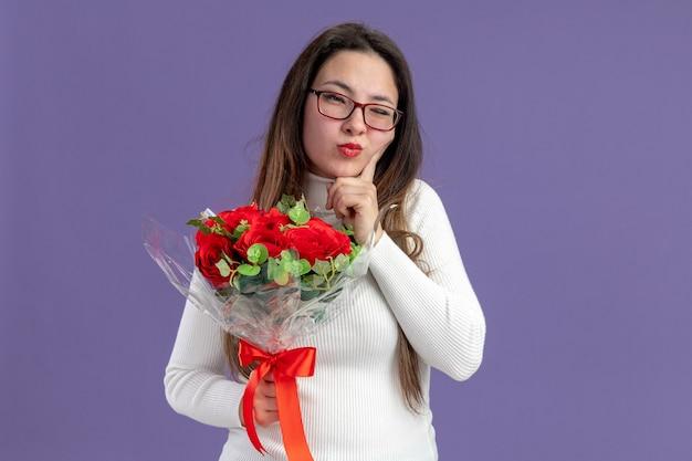 Młoda Piękna Kobieta W Codziennych Ubraniach Trzyma Bukiet Czerwonych Róż Patrząc Na Kamery Z Zamyślonym Wyrazem Twarzy Koncepcja Walentynki Stojąca Na Fioletowym Tle Darmowe Zdjęcia