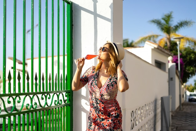 Młoda piękna kobieta w krótkiej sukience przechodzi ulicami małego europejskiego miasteczka. Darmowe Zdjęcia