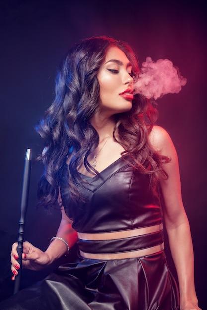 Młoda, Piękna Kobieta W Nocnym Klubie Lub Barze Pali Fajkę Wodną Lub Sziszę Premium Zdjęcia