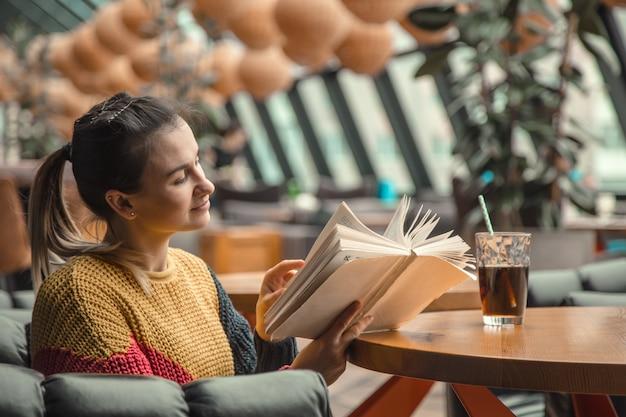 Młoda Piękna Kobieta W Pomarańczowym Swetrze Czyta Ciekawą Książkę W Kawiarni Darmowe Zdjęcia