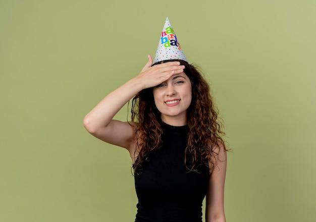 Młoda Piękna Kobieta Z Kręconymi Włosami W Czapce Wakacje Patrząc Zdezorientowany Uśmiechając Się Ręką Nad Głową Koncepcja Przyjęcie Urodzinowe Stojąc Nad Pomarańczową ścianą Darmowe Zdjęcia