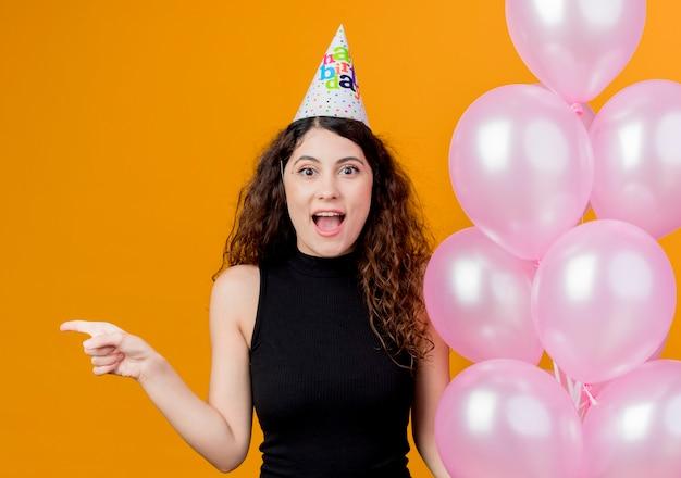 Młoda Piękna Kobieta Z Kręconymi Włosami W Czapce Wakacyjnej Trzymająca Balony Z Powietrzem Szczęśliwa I Podekscytowana, Wskazująca Palcem Na Bok Koncepcja Przyjęcia Urodzinowego Stojącego Nad Pomarańczową ścianą Darmowe Zdjęcia
