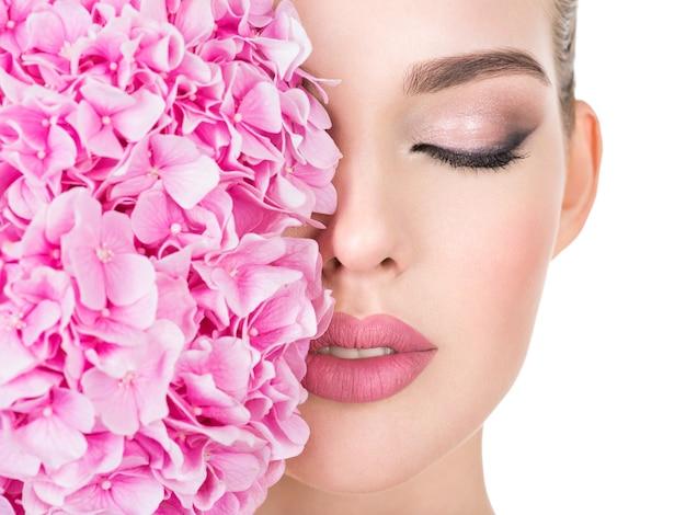 Młoda Piękna Kobieta Z Kwiatami W Pobliżu Twarzy. Darmowe Zdjęcia