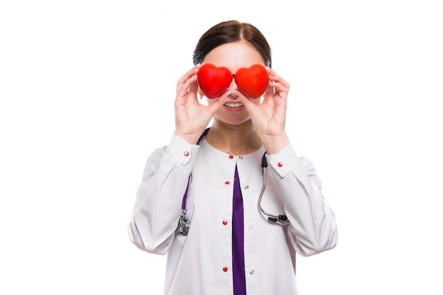 Młoda piękna kobiety lekarki mienia serca w jej rękach za ona kierownicza Premium Zdjęcia