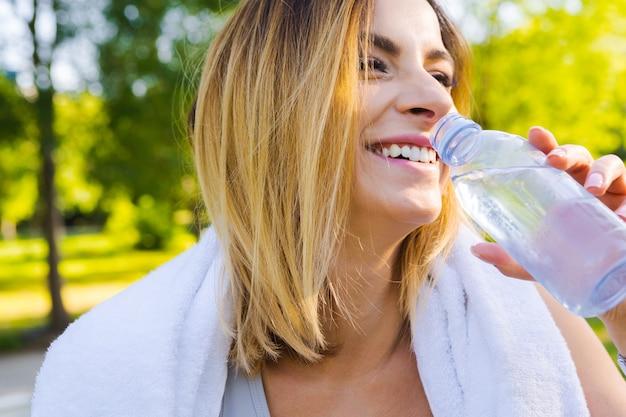 Młoda piękna kobiety woda pitna podczas ranku jogging w parku Premium Zdjęcia