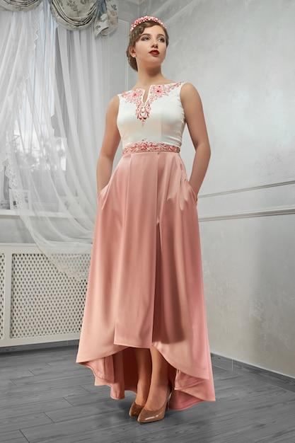Młoda Piękna, ładna Kobieta W Brzoskwiniowej Długiej Sukni, Ręka Na Biodrze, Kibel Darmowe Zdjęcia