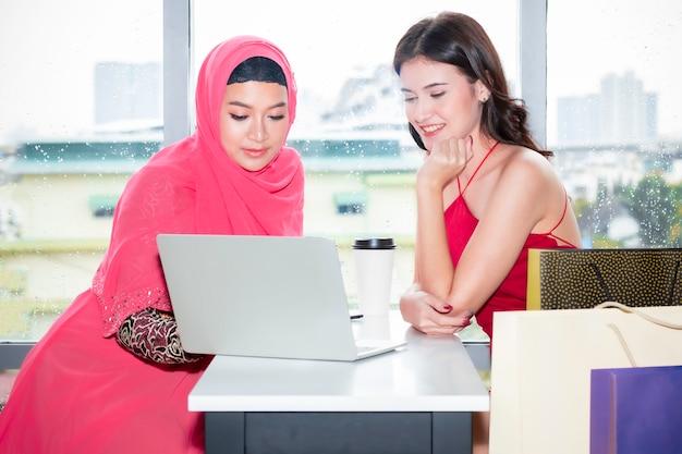Młoda piękna muzułmańska kobieta i kaukaskie przyjaźnie z torbami na zakupy i pastylką cieszy się w zakupy w sklep z kawą. pani wybiera zakupy online. Premium Zdjęcia