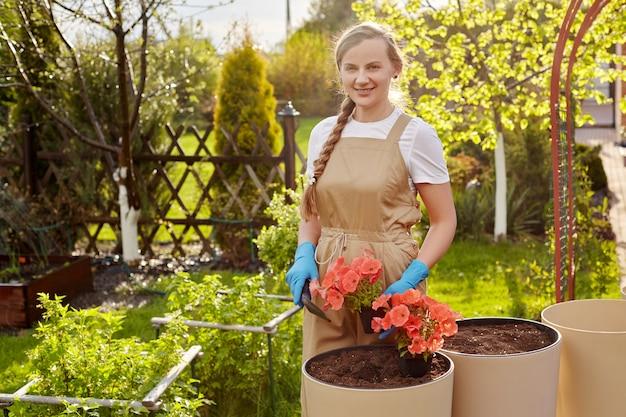 Młoda Piękna Ogrodniczka Przeszczepia Kwiaty Do Dużych Ceramicznych Wazonów W Ogrodzie. Premium Zdjęcia