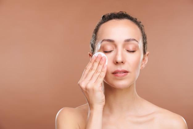 Młoda Piękna Pani Myje Twarz Balsamem Tonizującym Rano Lub Wieczorem Po Demakijażu Premium Zdjęcia