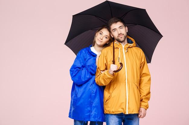 Młoda Piękna Para Pozuje W Podeszczowych Płaszczach Trzyma Parasol Nad światłem - Różowa ściana Darmowe Zdjęcia