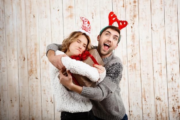Młoda Piękna Para Walczy O Prezent Na Boże Narodzenie Na Drewnianej ścianie Darmowe Zdjęcia