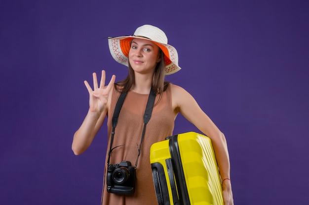 Młoda Piękna Podróżniczka Kobieta W Kapeluszu Lato Z żółtą Walizką I Aparatem Pozytywny I Szczęśliwy Uśmiechnięty Pokazujący Numer Trzy Na Fioletowej ścianie Darmowe Zdjęcia