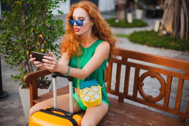 Młoda Piękna Seksowna Kobieta, Styl Hipster, Rude Włosy, Podróżnik, Zielony Top, Szorty, Pomarańczowa Walizka, Wakacje, Podróże, Siedzenie, Czekanie, Trzymanie Smartfona, Okulary Przeciwsłoneczne, Słuchanie Muzyki, Słuchawki Darmowe Zdjęcia