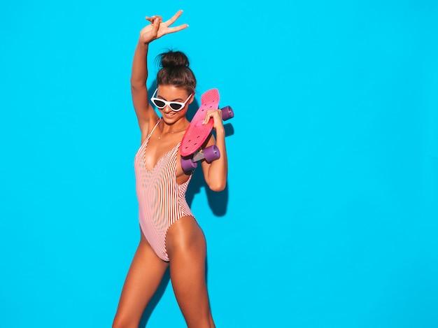 Młoda Piękna Seksowna Uśmiechnięta Modniś Kobieta W Okularach Przeciwsłonecznych. Modna Dziewczyna W Lato Stroju Kąpielowego Kostiumie Kąpielowym. Pozytywna Kobieta Oszalała Z Deskorolka Różowy Grosz, Odizolowane Na Niebiesko. Darmowe Zdjęcia