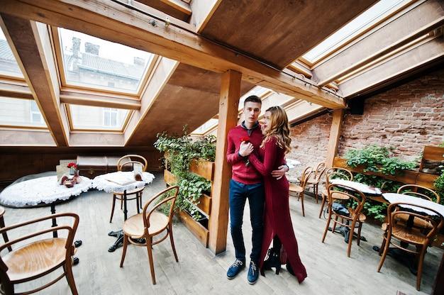 Młoda piękna stylowa para w czerwonej sukience w historii miłosnej w kawiarni vintage z dużymi oknami na dachu Premium Zdjęcia