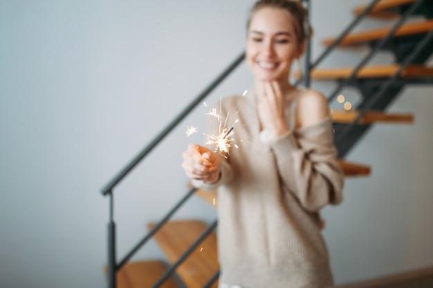 Młoda Piękna Szczęśliwa Dziewczyna Z Blond Włosy W Jedwabnej Sukni I Wygodnym Beżowym Kardiganem Trzyma Sparklers W Domu, Selekcyjna Ostrość Premium Zdjęcia