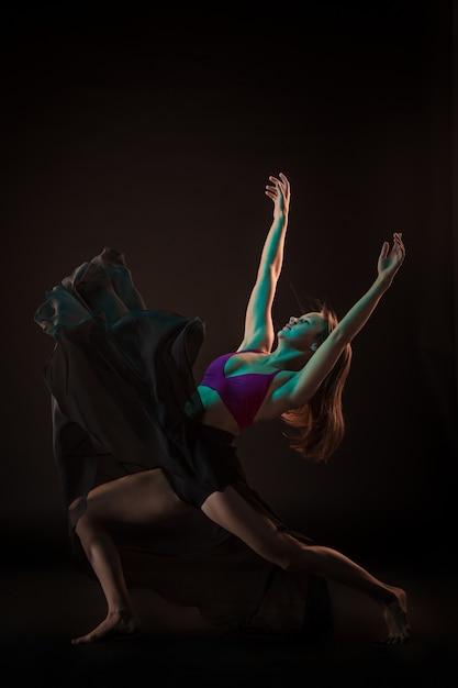 Młoda Piękna Tancerka W Beżowej Sukience Tańczy Na Czarnej ścianie Darmowe Zdjęcia
